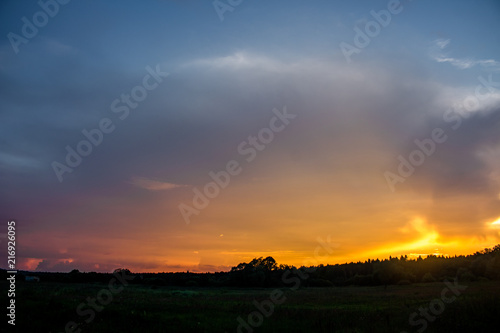 Bright beautiful sunset against a forest background on the horizon - 216926095