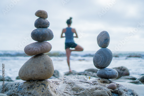 Plexiglas Zen Stenen Beautiful girl tree pose yoga by the ocean with stacking rocks