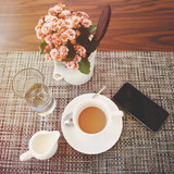 White cup of black coffee with a saucer, a vase with pink flowers, a glass with water, a creamer and a smartphone on a linen napkin on the table. Top view.