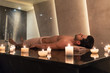 Quadro Young man relaxing on massage table surrounded by scented candles at Asian spa and wellness center