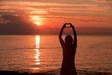 Silhouette of woman hands in heart shape with  red colored magic sunset. - 216944463