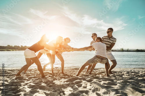 Leinwandbild Motiv Friends funny tug of war on the beach under sunset sunlight in sun