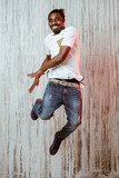 Ethnic man jumping and smiling near wall