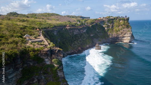 Foto Spatwand Blauwe hemel Aerial view at Pura Luhur Uluwatu temple. Stone cliffs, ocean waves and ocean landscape. Bali island, Indonesia.