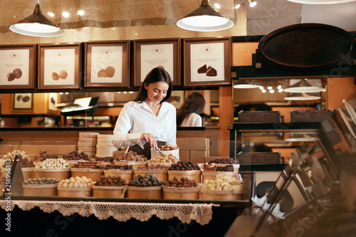 Foto Murales Confectionery. Woman Selling Chocolate Candies In Store