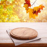Wooden table with empty board for pizza and tablecloth. Autumn background top view mock up. Selective focus. - 216959083