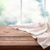 Empty wooden table with tablecloth near the window in kitchen. Napkin close up top view mock up. Kitchen rustic background with window. - 216959096