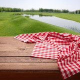 Red checkered tablecloth on wooden table. Napkin close up top view mock up. Summer rustic background. - 216959222