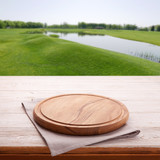 Wooden table with empty board for pizza and tablecloth. Summer background top view mock up. Selective focus. - 216959257