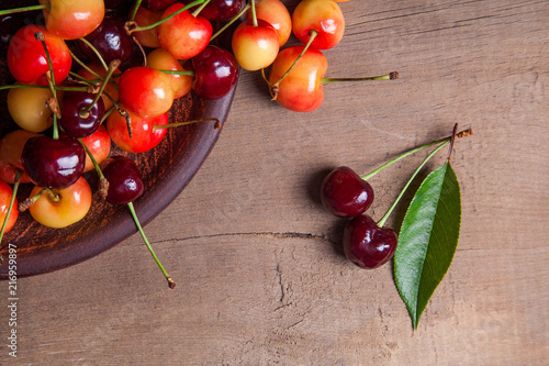 Foto Spatwand Kersen Clay plate with yellow and red sweet cherry on wooden background.