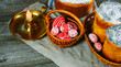 Red easter eggs with folk Ukrainian pattern lay into basket beside easter cakes and candlestick on sheet of vintage cloth on old wood background. Ukrainian traditional eggs pisanka and krashanka