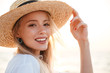 Cute blonde woman wearing hat outdoors at the beach