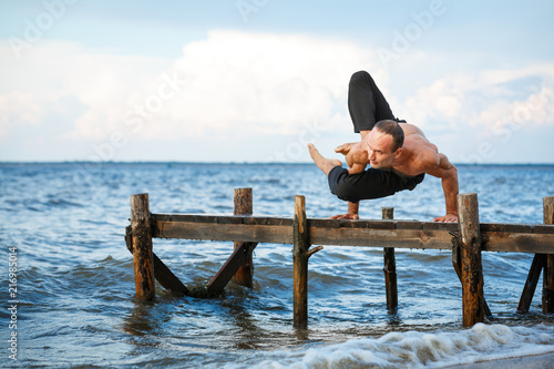 Plakat Young yoga trainer practicing yoga exercises on a wooden pier on a sea or river shore.