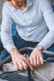 selective focus of businessman with wristwatch packing luggage in suitcase - 216987222
