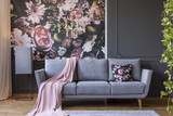 Powder pink blanket thrown on grey couch in real photo of dark sitting room interior with floral wallpaper, gold lamp and wainscoting on wall