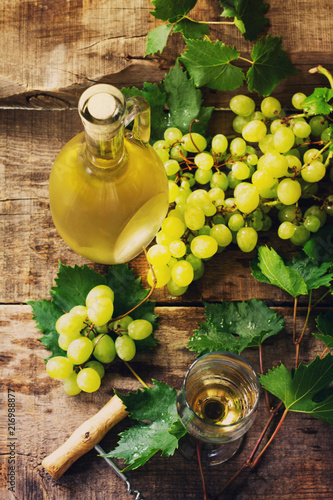 Wine background. White wine in glasses, bottle, grapes on vintage background, wine concept. Toned image. © elena_hramowa