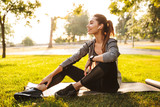Fitness sports woman in park outdoors listening music with earphones.