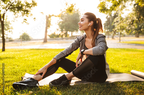 Poster Fitness sports woman in park outdoors listening music with earphones.