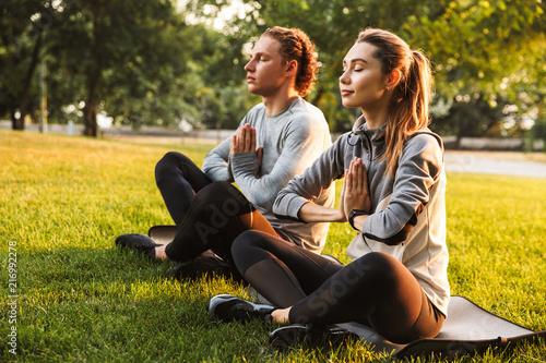 Foto Murales Fitness loving couple friends in park make meditate exercises.