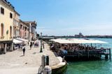 A street in Venice, Italy, with restaurant on water and people enjoying the sunshine