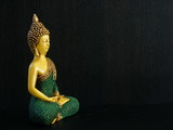 Image of Buddha seen from a side over a dark background.