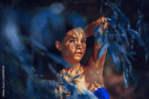 Foto Murales Beautiful young woman in a bikini in the shade under the tree