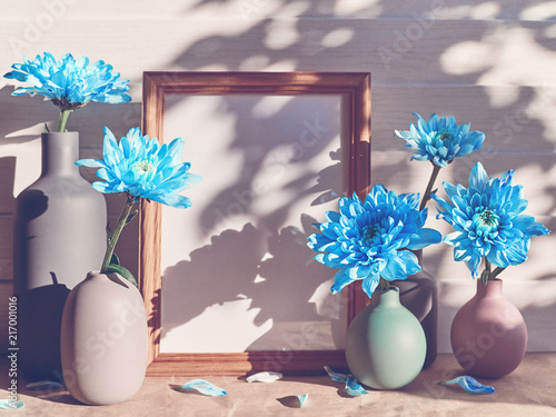 Blue Chrysanthemums Are In Different Vases In The Center Of The