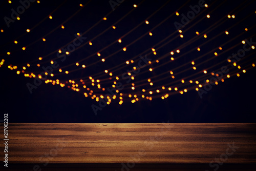 Image of wooden table in front of abstract blurred city golden garland lights background. - 217002202