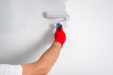 Painter hand painting a wall with paint roller - 217002854