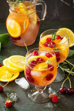Homemade refreshing wine sangria or punch with fruits in glasses. Sangria cocktails with fresh fruits, berries and rosemary. On a stone or slate background, with a jug and ingredients.