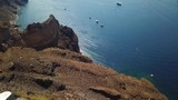 Aerial drone shot from houses on a cliff down the hill to boats in the water in Santorini Greece - 217009076