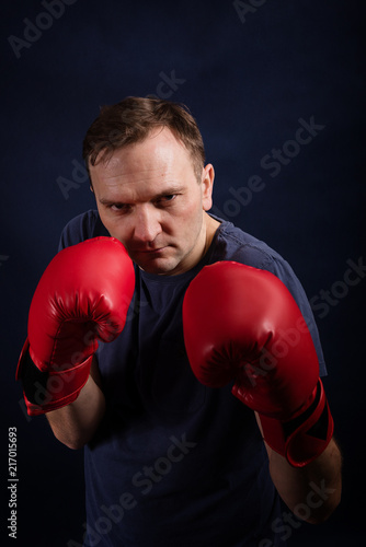 Middle aged boxer amateur trains on a dark background
