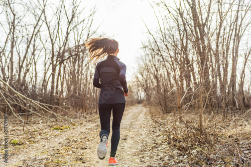 Autumn run sport athlete woman training on outdoor park. Trail runner running in fall nature forest.