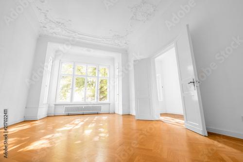 Leinwanddruck Bild empty room in old apartment building with wooden parquet floor