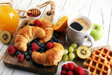 Delicious breakfast with fresh croissants and ripe berries on table - 217026830
