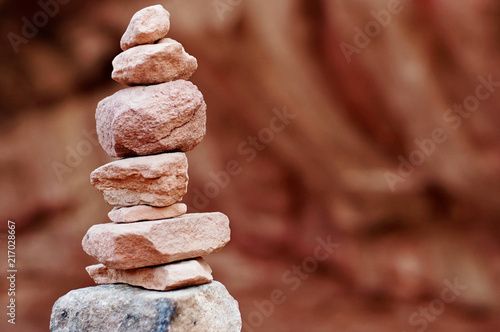Canvas Diepbruine balanced stack of rocks with red mountains on the back