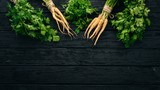 Fresh green parsley. Root parsley. On a wooden background. Top view. Copy space. - 217037288
