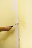 Hand applying paint on wall