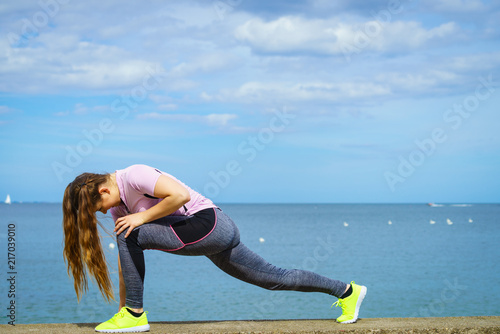 Plakat Woman stretching legs next to sea