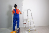 Woman at painting a room with paint roller - 217041667