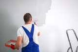 Painter man at work with a paint roller - 217042012