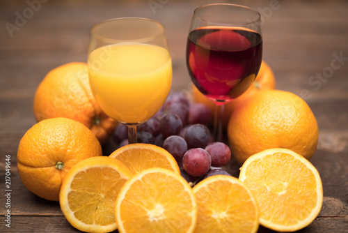 Canvas Sap Juice glass and grape and orange fruit on wooden background