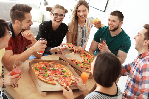 Young people having fun party with delicious pizza indoors - 217064447