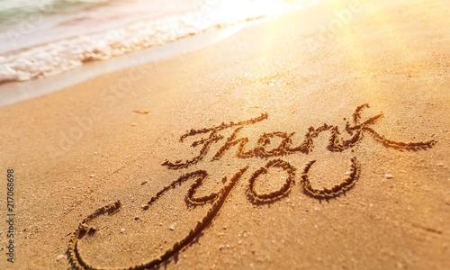 Leinwanddruck Bild Thank you sign on sandy sea beach