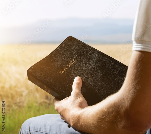 Foto Murales Man reading old Bible book on background
