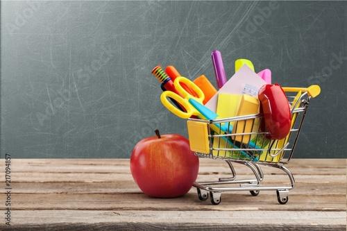 Leinwandbild Motiv Stationery objects in mini supermarket cart
