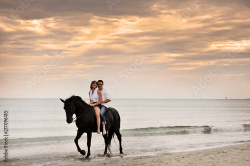 couple and horse on the beach