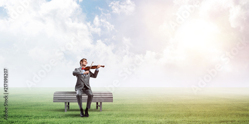 Foto Murales Handsome businessman in park on wooden bench play his melody