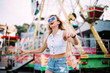Quadro Stylish happy young woman wearing short denim shorts and a white T-shirt. brightred lips . portrait of smiling girl in sunglasses greet friends and laughter