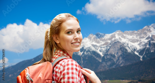 Foto Murales adventure, travel, tourism, hike and people concept - smiling young woman with backpack over alps mountains background